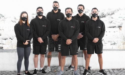 En kvinne og fem menn kledd i svart med munnbind.