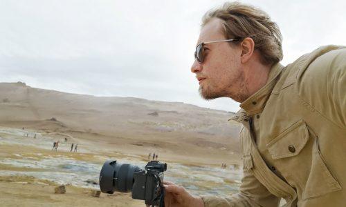 En mann i profil kledd i beige med solbriller. Han holder et kamera.